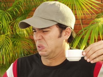 chico bebiendo cafe con mala cara